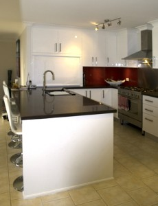 White kitchen with red glass splashback